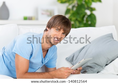 man lying on the sofa reading tablet - stock photo