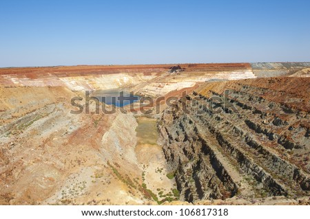 Man made deep hole for open cut mining in outback Australia, close to Meekatharra in Western Australia, panoramic view with copy space. - stock photo