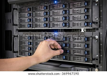man maintenance hardisk on network attached storage (NAS) - stock photo