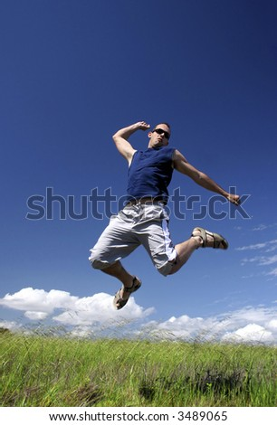 Man make a big jump on a green meadow