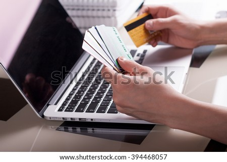man make electronic payment via laptop computer and credit card sitting at the glass table with books at the background