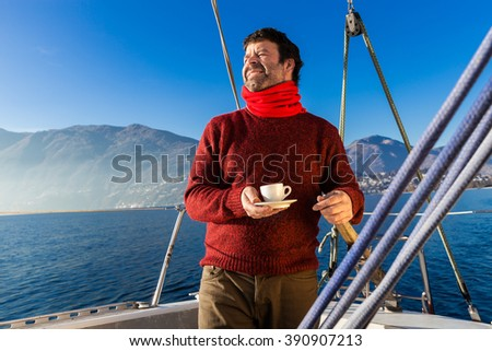 man makes a coffee break aboard his sailboat