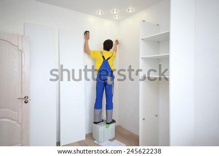 Man makes a mark on the wall to install a corner sliding wardrobe - stock photo