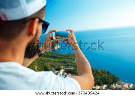 Man makes photos by a smartphone on the background of sea coast, Adriatic sea, Montenegro, Balkans - stock photo