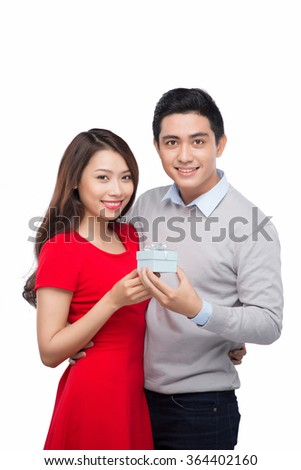 Man makes present to his lovely sweetheart. Young man giving a gift - stock photo