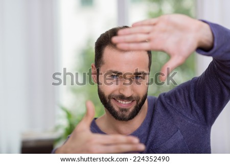 Man making a frame gesture with his hands as he visualises a project or image - stock photo