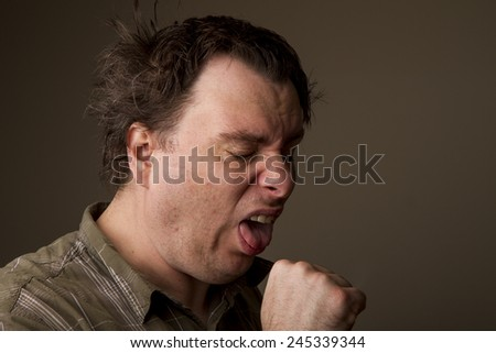 man making a funny face while coughing into his hand - stock photo