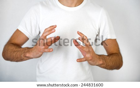 Man making a hand gesture to clasp a round object with his hands on opposite sides and fingers spread, blank space in between over his white t-shirt - stock photo