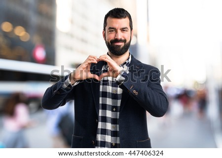 Man making a heart with his hands on unfocused background - stock photo