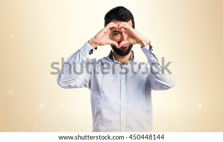 Man making a heart with his hands over ocher background - stock photo