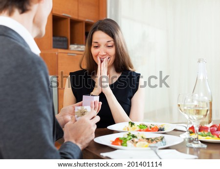 man making a woman marriage proposal for a romantic dinner with champagne - stock photo