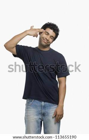 Man making gun sign with fingers at his head - stock photo