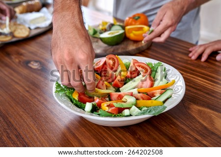 man making healthy fresh salad in kitchen - stock photo