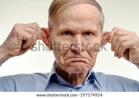 Man making  monkey face. Senior man stretching his ears. Man making funny face. - stock photo