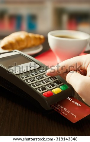 Man making payment with terminal for sale in cafeteria or restaurant - stock photo