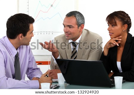 Man making point in business meeting - stock photo