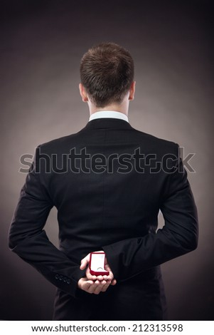 Man making proposal with wedding ring and red gift box. - stock photo