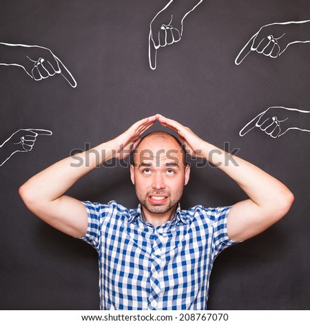 Man making protective gesture at someone's  pointed hands - stock photo