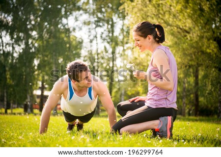 Man making push-ups while woman is blowing dandelion seeds on him - outdoor in nature - stock photo