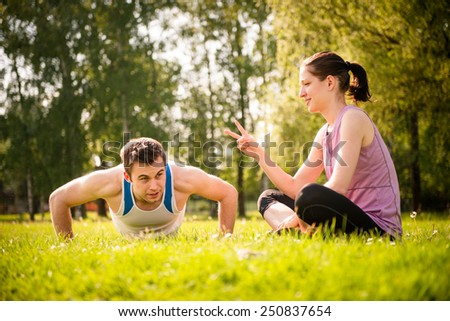Man making push-ups while woman is counting their number - outdoor in nature - stock photo