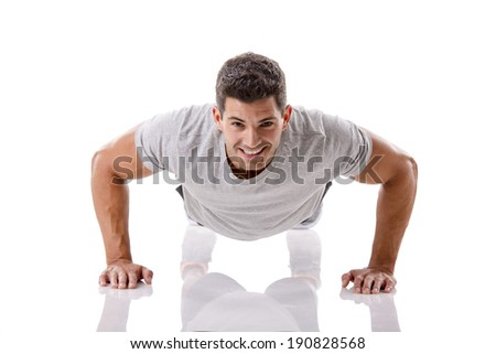 Man making pushups in studio, isolated over a white background - stock photo