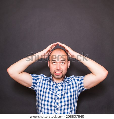 Man making roof with hands above his head - stock photo