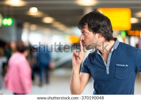 Man making silence gesture on unfocused background
