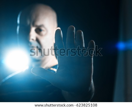 Man making stop sign, rejective hand gesture, on the black