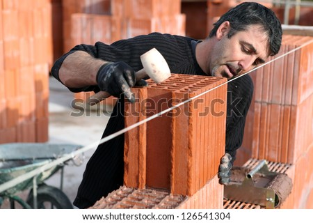 Man making sure wall is straight - stock photo