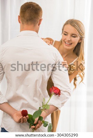 Man making surprise. His wife looking behind his shoulder what he want to present. - stock photo