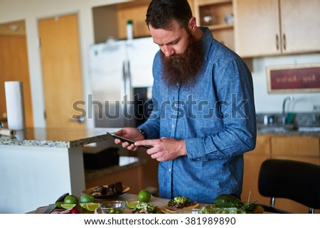 man making tacos in kitchen and using tablet to look up recipe shot with selective focus - stock photo