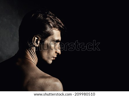 Man. Male portrait in profile on black background. - stock photo