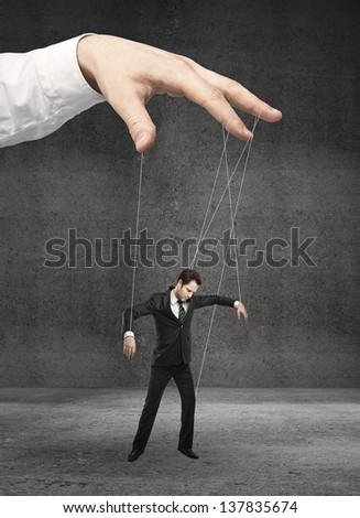man marionette on ropes controlled  hand - stock photo