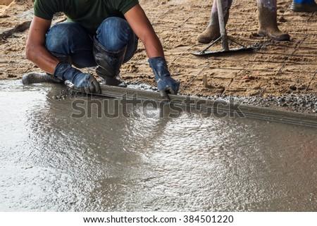 Man mason building a screed coat cement on floor - stock photo