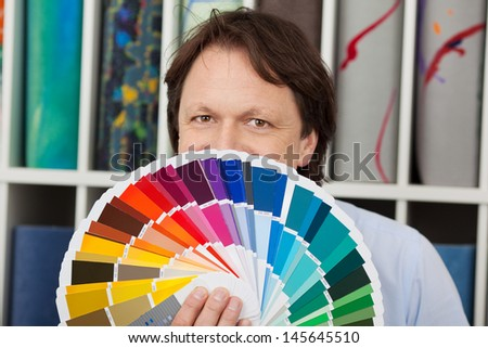 Man matching paint and carpet colors standing in front of the carpet display showing the color charts for the paint - stock photo