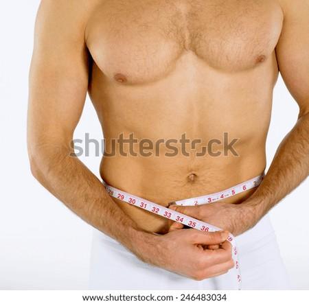 Man measuring his waist - stock photo