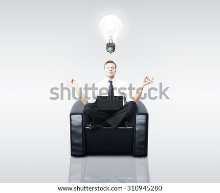 man meditating in a chair with a laptop - stock photo