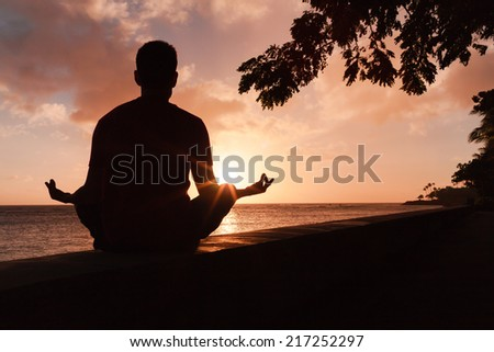 Man meditating in an yoga pose on the beach