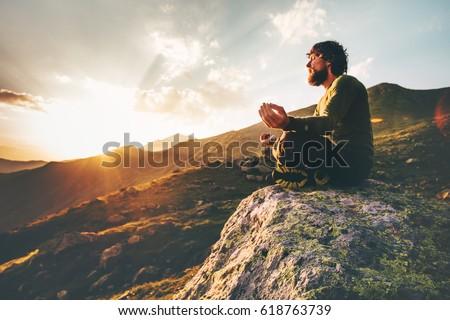 man meditating yoga lotus pose sunset stock photo