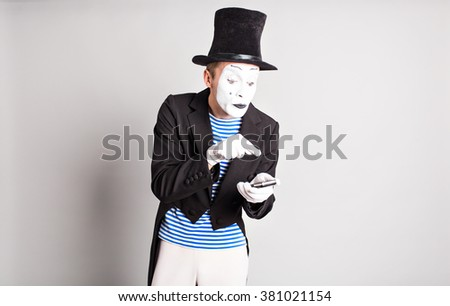Man mime  holding cell phone. April Fool's Day concept. - stock photo