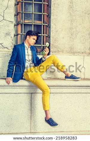 Man Missing You. Dressing in blue blazer, yellow pants, casual sneakers, a young handsome guy is sitting by a window on street, looking at white rose on hand, thinking.