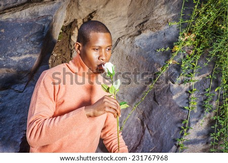 Man Missing You. Dressing in light orange sweater with high collar,  a young black guy is standing against rocks with long leaves, holding a white rose, looking down, smelling, thinking.  - stock photo