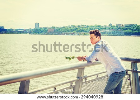 Man Missing You. Wearing white shirt, jeans, holding white rose, a guy standing by Hudson River in New York, opposite New Jersey, thinking, lost in thought. Concept of looking for love, friendship.