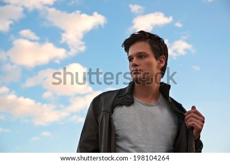 man model in brown leather jacket on blue sky background