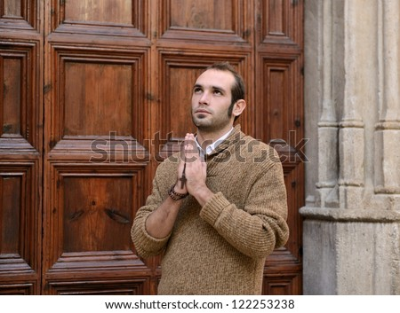 man monk praying to the front door of the church holding  rosary - stock photo