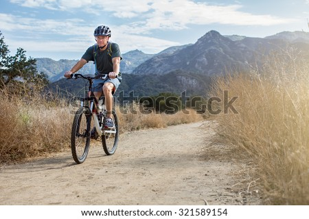 Man mountain biking wearing a water backpack - stock photo