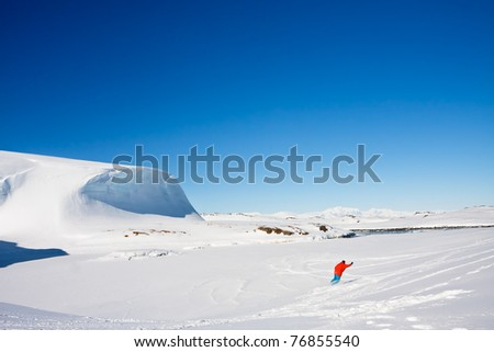 Man moves on skis. Glacier in background. Antarctica