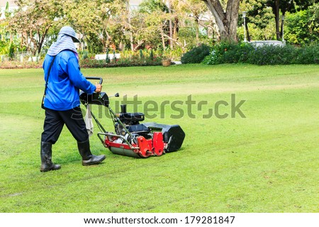 Man moves with lawnmower when gardening