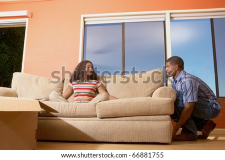 Man moving couch with woman sitting on it - stock photo