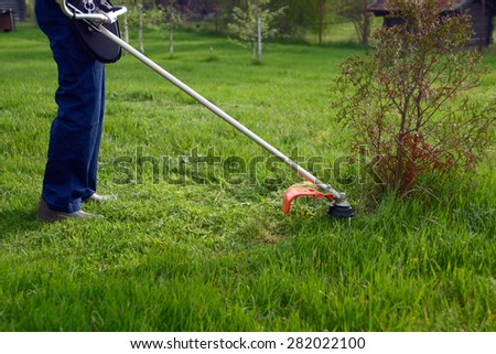 Man mowing grass with petrol weed trimmer - stock photo
